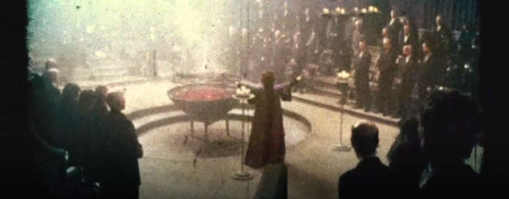 A grainy image of a religious ritual is seen. A crowd of people dressed in all black encircle Christabella. In front of Christabella is a blackened child being burned alive over hot coals.