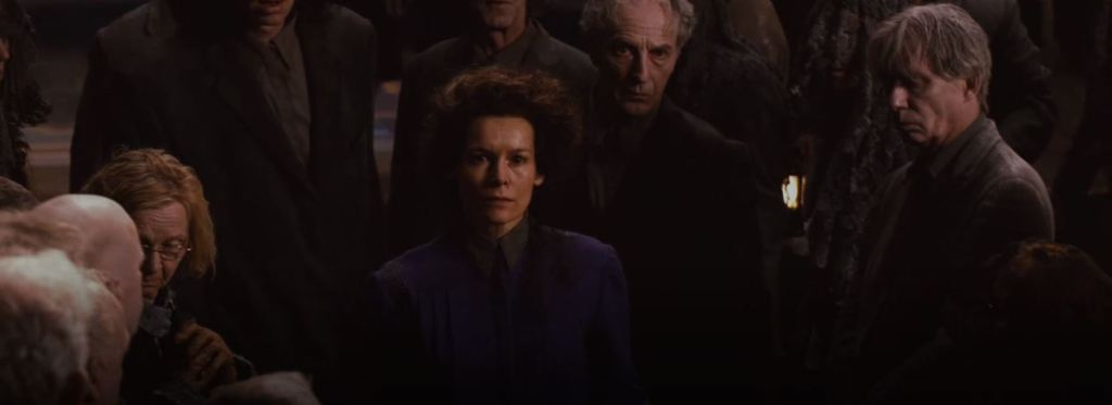 A severe looking white woman in a long sleeved purple dress with her brown hair pinned up stares at Cybil and Rose.