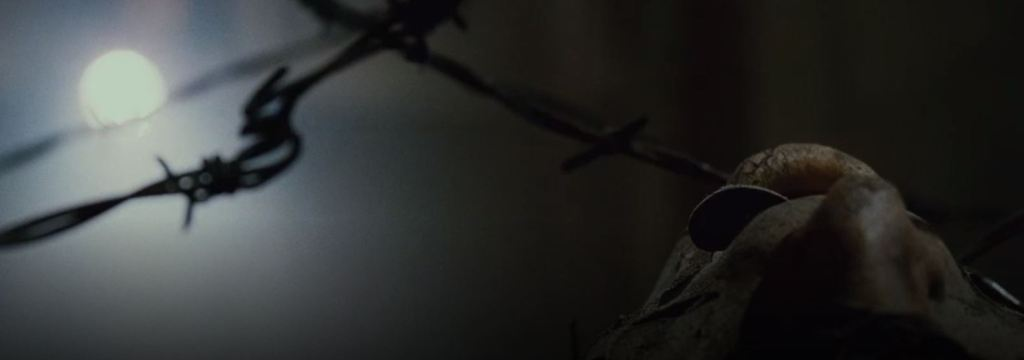 The face of a corpse is seen looking up at the ceiling with a key sticking out of its mouth. There is barbed wire holding it in place.