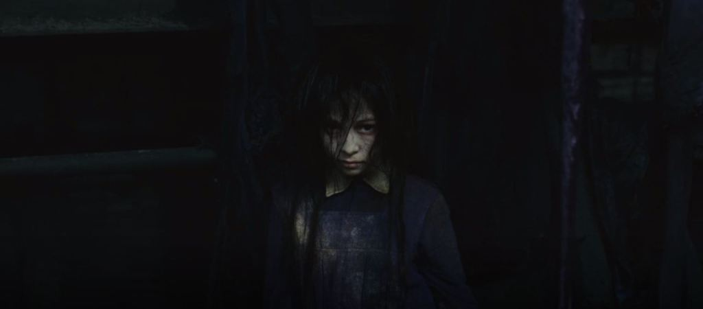 An ash covered little girl with dark, stringy black hair is seen from the stomach up.